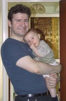 My son, David, standing in a doorway with baby Andrew in his arms (5th September 2004)